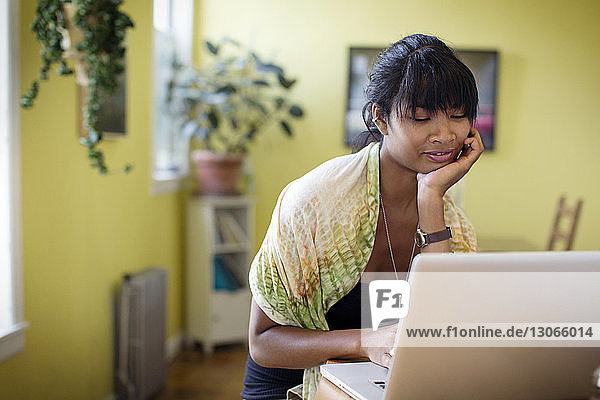 Woman with hand on chin using laptop computer at home