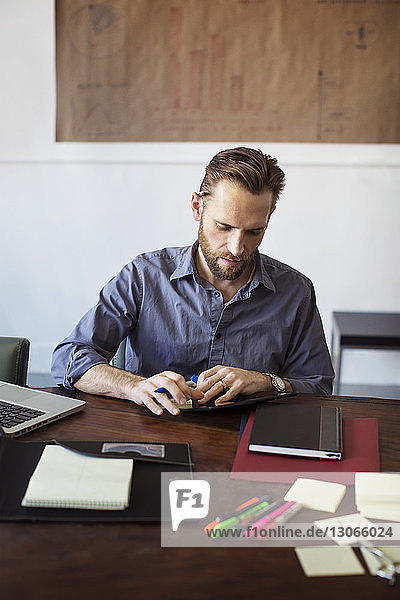 Man using tablet computer while working in office