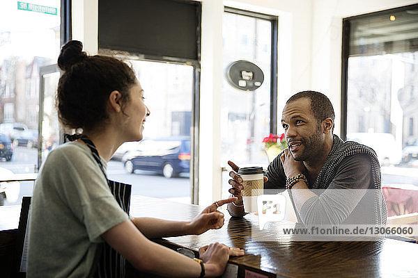 Mann mit Tasse in der Hand spricht mit Besitzer im Café