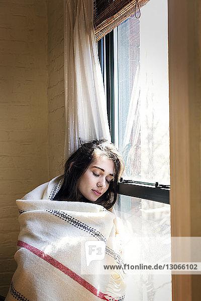Frau mit geschlossenen Augen  die zu Hause am Fenster lehnt