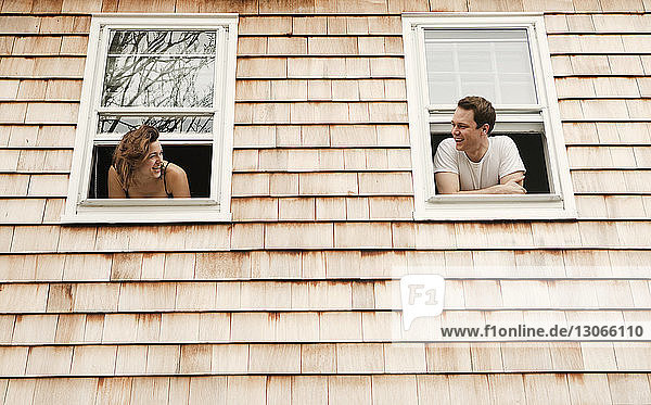 Couple leaning on windows at home