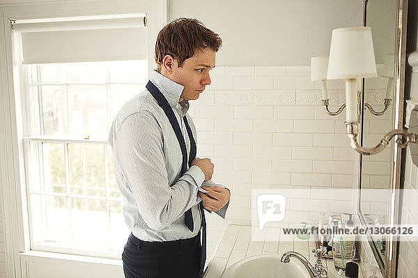 Side view of man getting dressed while standing at bathroom sink