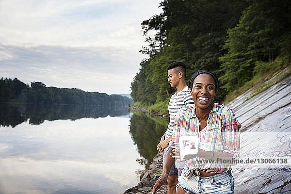 Lächelnde Frau mit am Seeufer stehendem Mann
