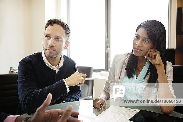 Geschäftsleute schauen weg  während sie im Büro am Tisch sitzen