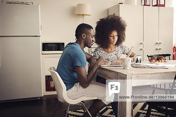 Couple having coffee while using laptop computer at table in kitchen