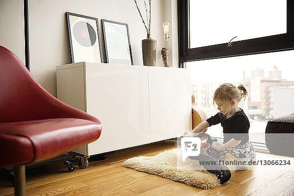 Mädchen nimmt Gitarre aus Koffer  während sie zu Hause sitzt