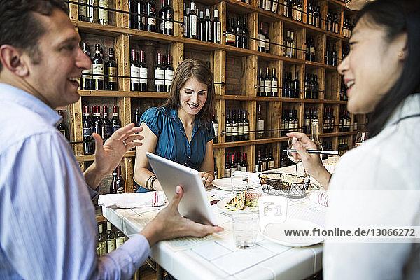 Geschäftsmann zeigt Tablet-Computer  während er in einer Bar sitzt