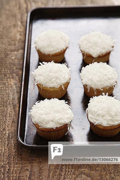 Hochwinkelansicht von Cupcakes im Tablett auf dem Tisch