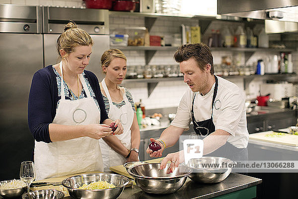 Männlicher Koch zeigt Studenten Früchte in Großküche