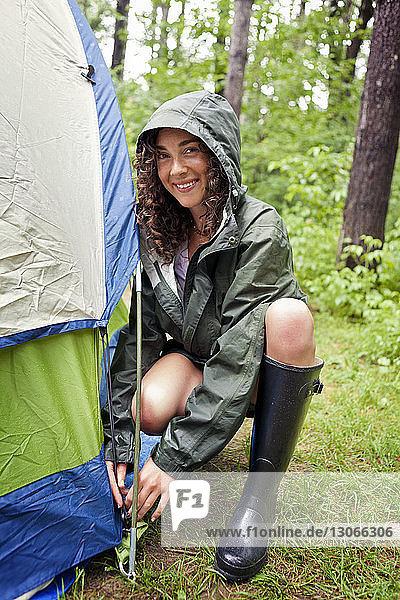Porträt einer Frau  die im Wald ein Zelt vorbereitet