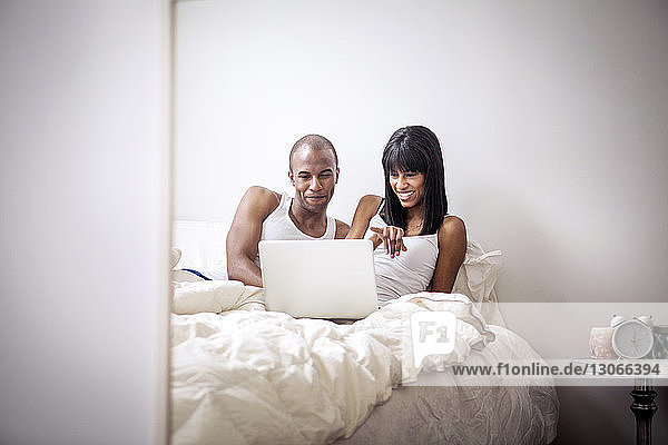 Couple looking at laptop computer while sitting on bed