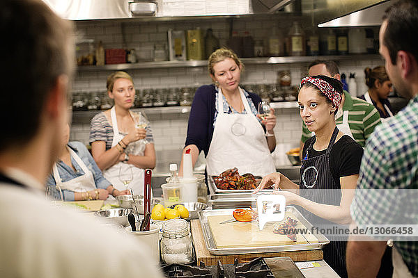 Female chef teaching students while standing at commercial kitchen