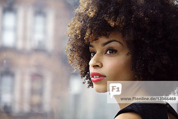 Close-up of thoughtful woman with curly hair looking away while standing by window