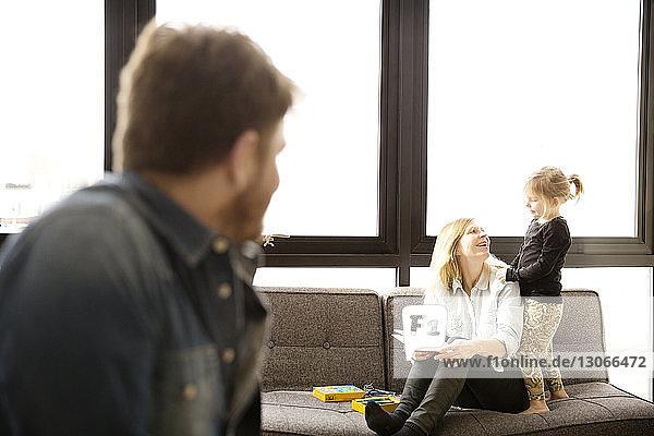 Mann sieht Frau an  die mit Tochter zu Hause sitzt