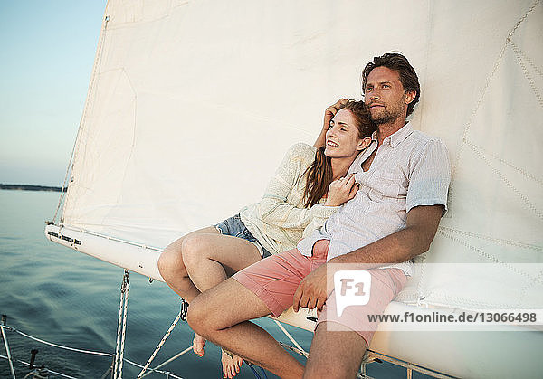 Männer reisen mit einer Yacht gegen den klaren Himmel Männer reisen mit einer Yacht gegen den klaren Himmel