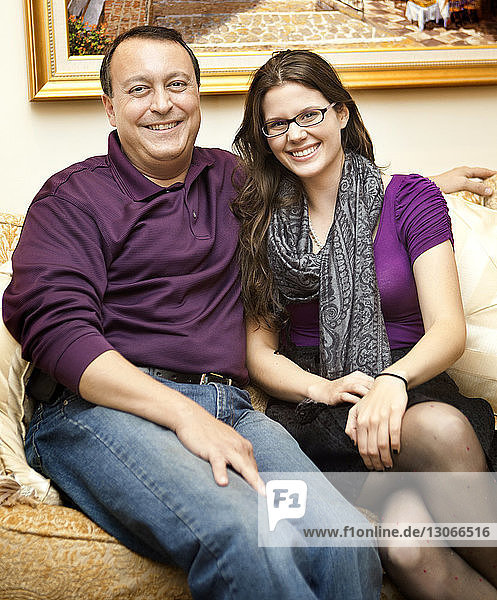 Portrait of father and daughter sitting on sofa at home