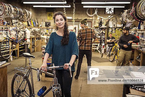 Porträt einer Frau  die ein Fahrrad hält  während sie mit ihren Kollegen im Hintergrund steht