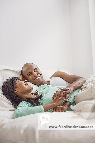Lächelndes Paar entspannt zu Hause im Bett