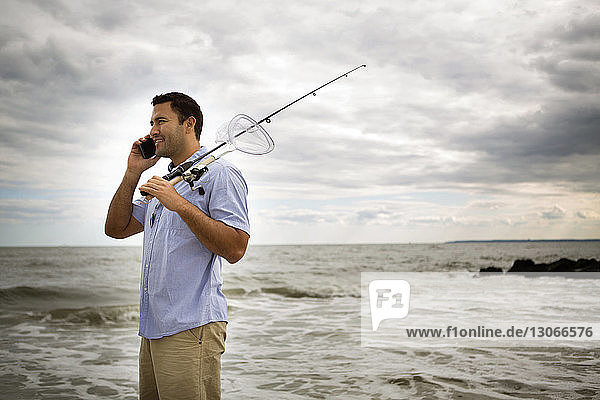 Man holding fishing rod talking on mobile phone while standing by sea