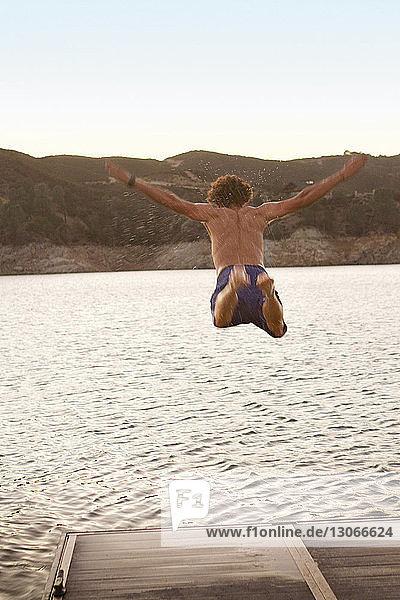 Rear view of man jumping in lake during sunset