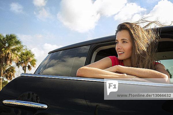 Frau schaut weg  während sie sich an die Autotür lehnt