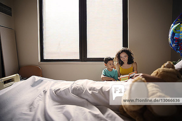 Mother and son reading book while sitting by patient in hospital ward