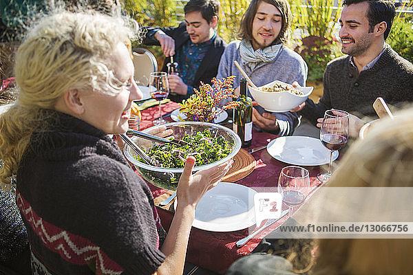 Freunde essen während der Gartenparty am Tisch im Freien