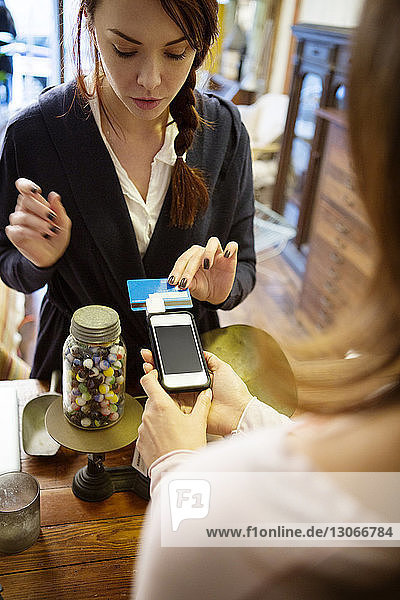 Customer paying through credit card at checkout counter in store
