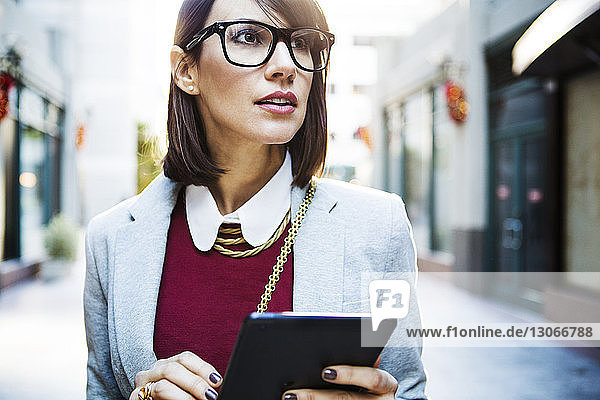 Woman looking away while holding tablet computer at city street