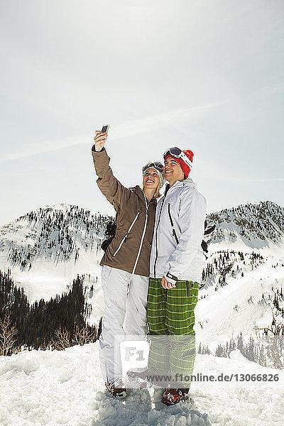Skifahrer klickt auf Selfie  während er auf einem schneebedeckten Berg steht