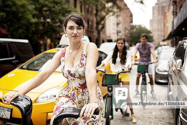 Porträt einer Fahrrad fahrenden Frau mit Freunden im Hintergrund