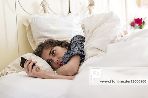 Frau benutzt Mobiltelefon,  während sie auf dem Bett liegt