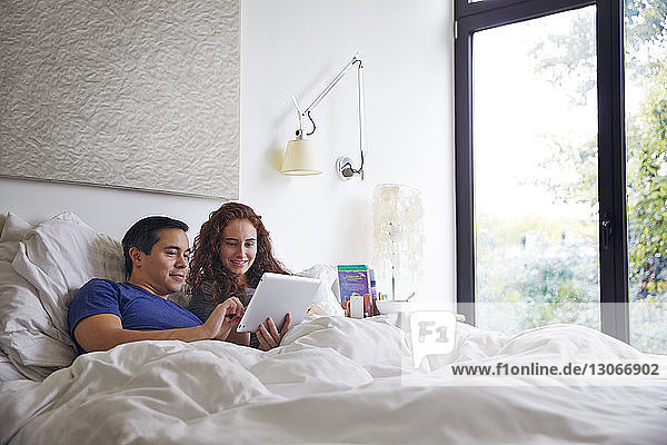 Smiling couple looking at tablet computer while lying on bed by window