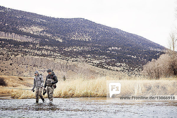 Couple fishing in lake while standing against mountain