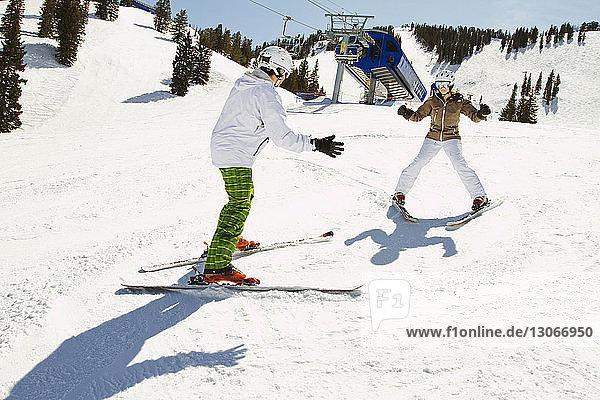Skifahren zu zweit auf schneebedecktem Feld
