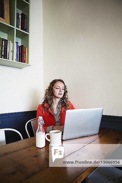 Frau benutzt Laptop-Computer  während sie im Café sitzt