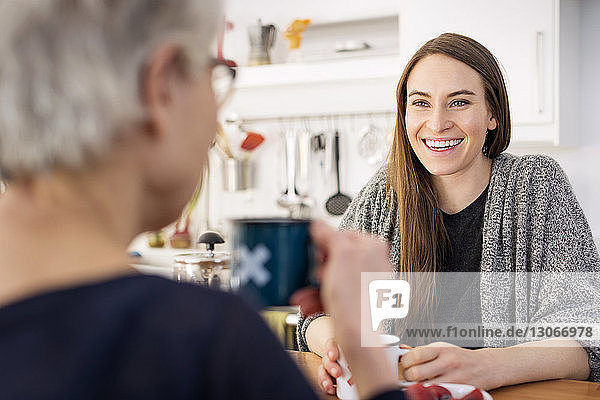 Woman sitting with mother at table in home