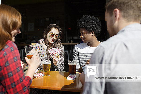 Smiling friends playing cards while having beer at table in brewery