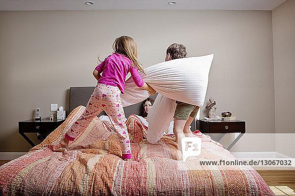 Kinder spielen Kissenschlacht mit den Eltern zu Hause im Bett