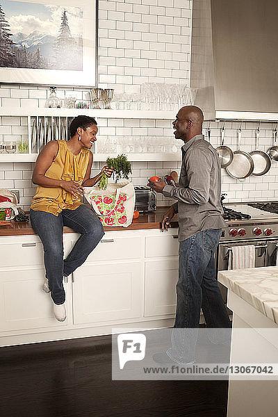 Fröhliches Paar nimmt in der Küche Gemüse aus der Einkaufstasche
