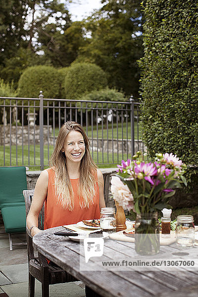 Happy woman sitting at breakfast table in lawn