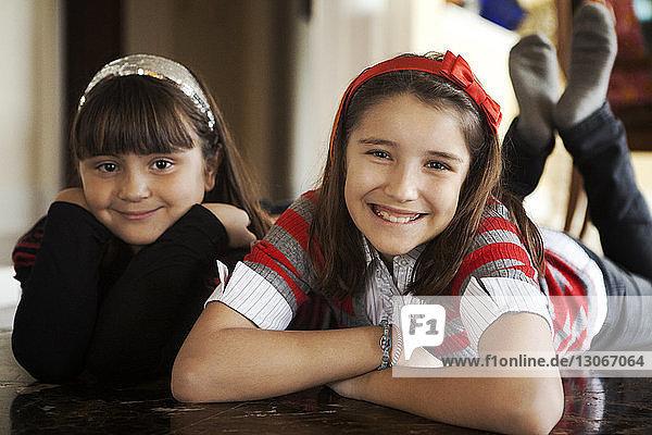 Porträt von glücklichen Schwestern  die zu Hause auf dem Boden liegen