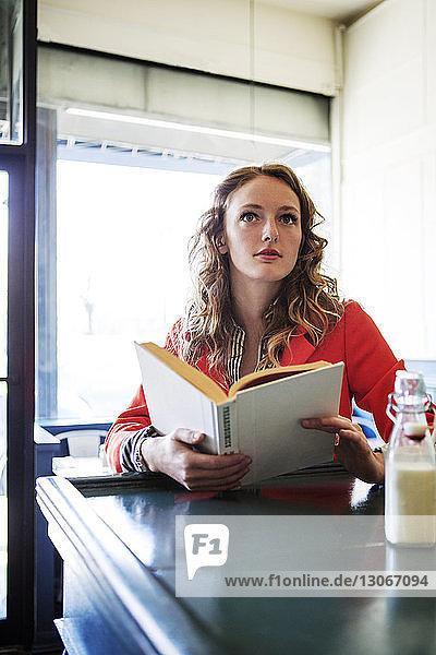 Frau mit Buch schaut im Café weg