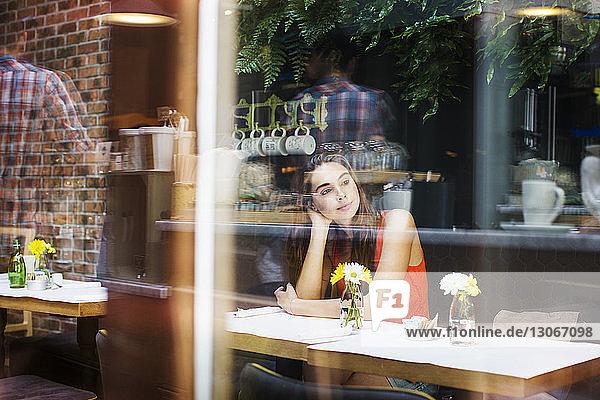Nachdenkliche Frau sitzt im Restaurant durch Glasfenster gesehen