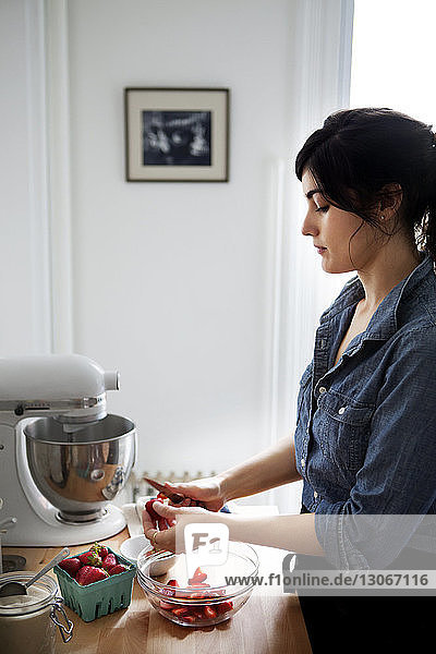 Woman cutting strawberries while standing in kitchen at home