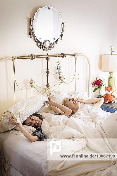 Fröhliche Freunde zu Hause im Bett