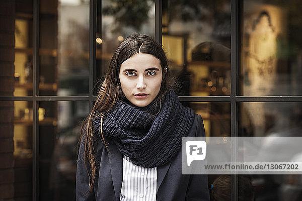 Porträt einer Frau  die vor Glasfenstern steht