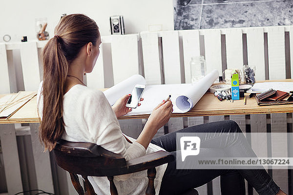 Side view of woman using smart phone while sitting on chair at home