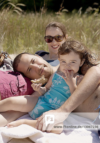 Portrait of family relaxing on field