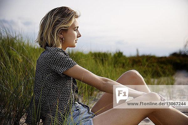 Seitenansicht einer Frau  die wegschaut  während sie auf Sand sitzt